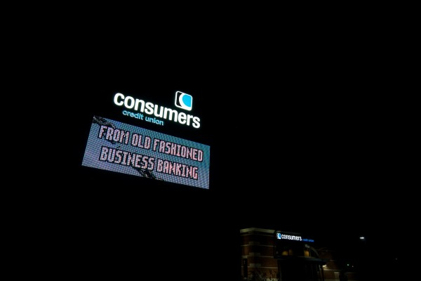 Consumers Credit Union illuminated monument sign with digital advertising electronic message center at night